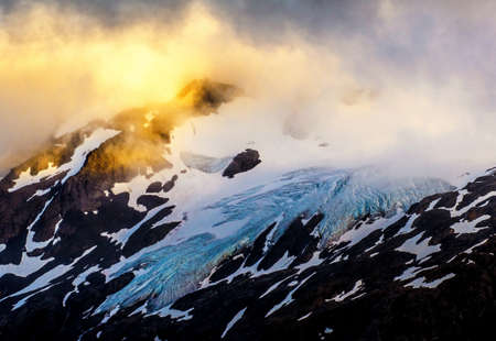 icefield: The golden light touches the peak of the mountain residing next to the glacier from the Harding Icefield in Alaska. Stock Photo
