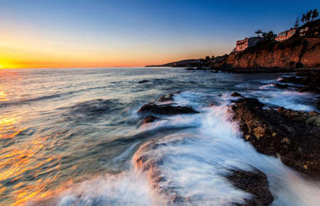 california coast: Beautiful sunset light touches the wave approaching the rocks. At Victoria Beach,