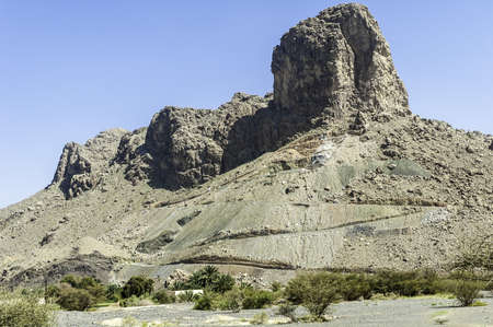 cliff face: Mountain with an imposing cliff face against a cloudless blue sky