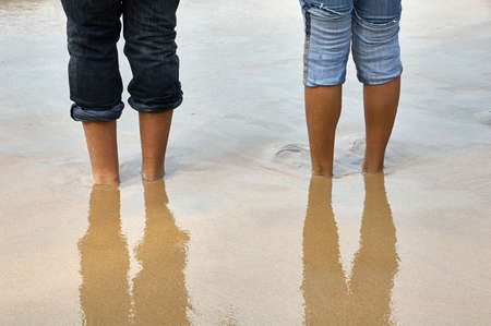 shoeless: Bare feet buried in the sand upto the ankles on a beach