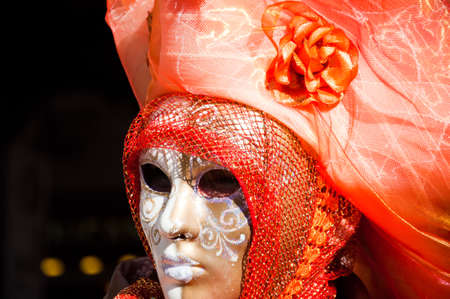 Venice Carnival - women with orange dress and white mask photo