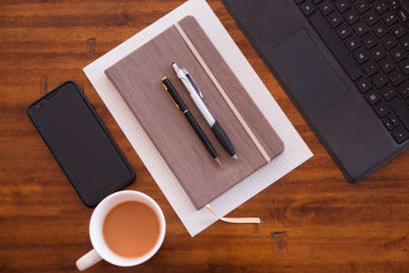 Hipster lifestyle. Working from home or at cafe or at the office. Computer, mobile device, smartphone, notebook, coffee and pens. Work anywhere. Working hard as an entrepreneur, small business
