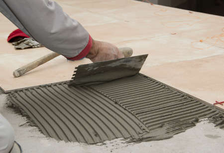 new construction renovation: Home improvement, renovation - handyman laying tile with level