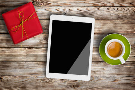 Gift box, cup of coffee and digital tablet on wooden background 版權商用圖片