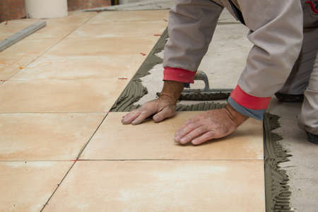 Home improvement, renovation - handyman laying tile with level