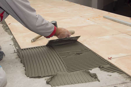 floor tiles: Home improvement, renovation - handyman laying tile with level
