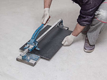 Construction worker cutting tiles for home renovation