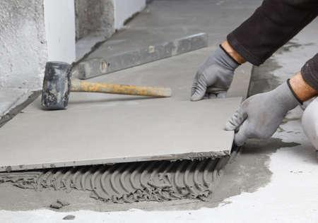 tile adhesive: Home improvement, renovation - construction worker tiler is tiling, ceramic tile floor adhesive, trowel with mortar