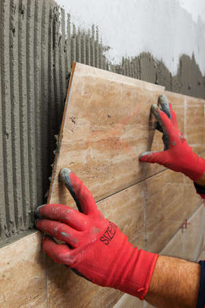 tiler: Ceramic Tiles. Tiler placing ceramic wall tile in position over adhesive Stock Photo