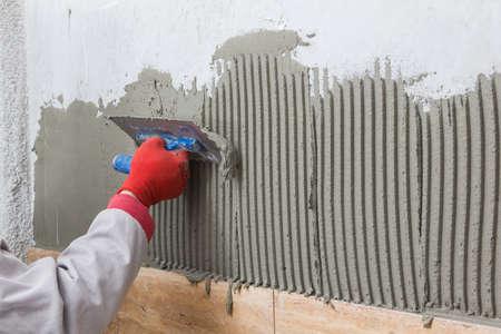 Ceramic Tiles. Tilerman hand spreading adhesive material 版權商用圖片