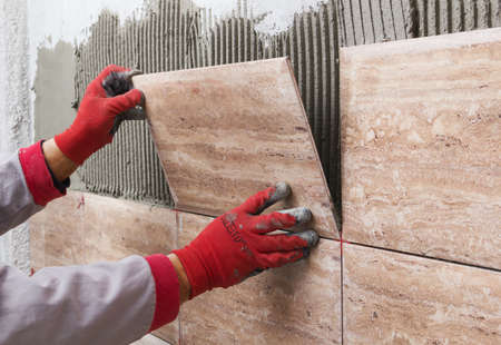 セラミック タイル。陶磁器の壁のタイルを接着剤で位置に置く瓦職人 写真素材