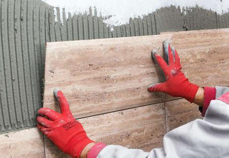 Ceramic Tiles. Tiler placing ceramic wall tile in position over adhesive 版權商用圖片