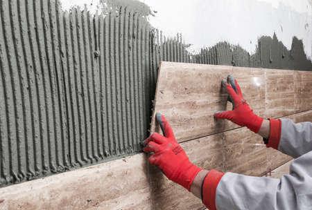 Verbetering van het huis, renovatie - bouwvakker tegelzetter is tegels, keramische tegels muur lijm