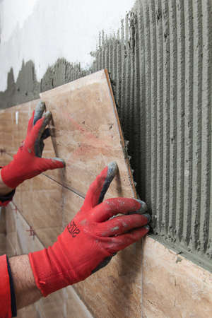 tile adhesive: Home improvement, renovation - construction worker tiler is tiling, ceramic tile wall adhesive Stock Photo
