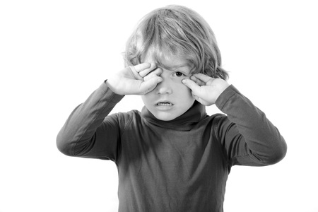 rubbing: tired child rubbing his eyes isolated on white background