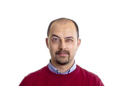 one eye: man blinks one eye isolated on white background Stock Photo