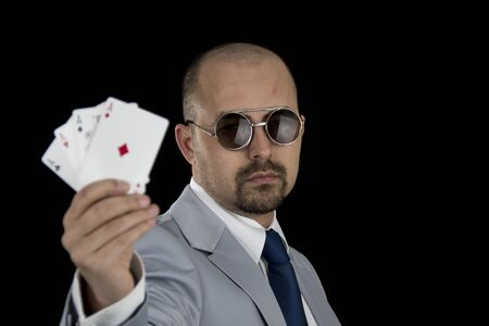 aces: man in business suit holding 4 aces poker playing cards in his hand isolated on black background Stock Photo