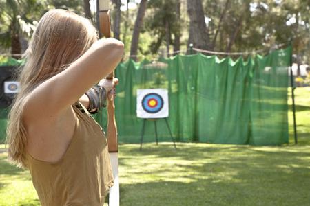 Mujer de tiro con arco apuntando a la diana Foto de archivo