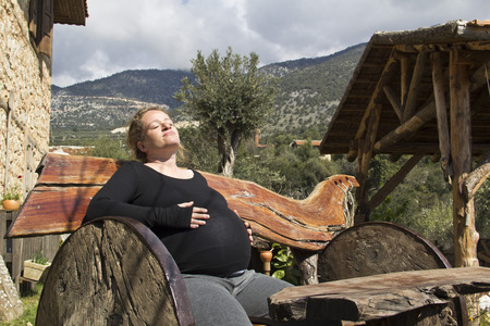 wooden bench: pregnant woman sunbathing on wooden bench Stock Photo