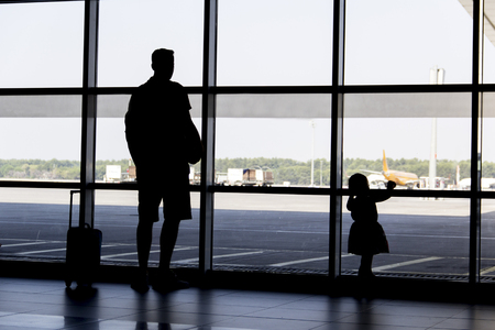 man and girl silhouette looking planes landing at airport