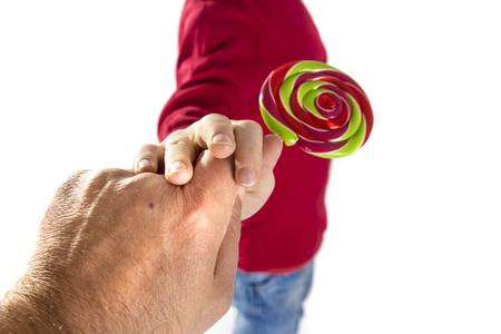 petite fille triste: main de l'homme donne des bonbons aux enfants