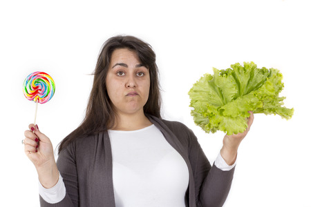 decided: large young woman decided for unhealthy or healthy food on white background