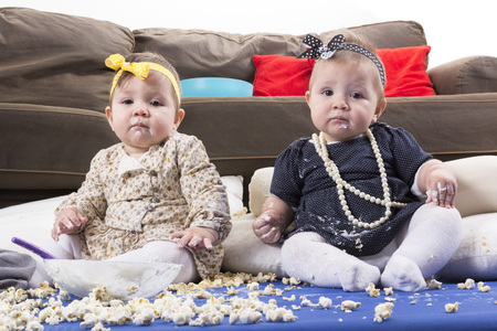 adorable twin babies playing with food