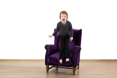 child tantrums angry screaming on an armchair Stock Photo