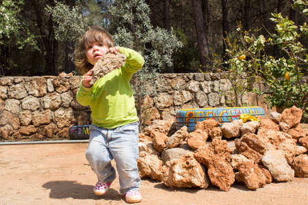 carying: child carying big rock in garden