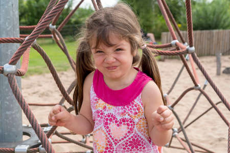 Angry face cute little girl in the park. Stock Photo