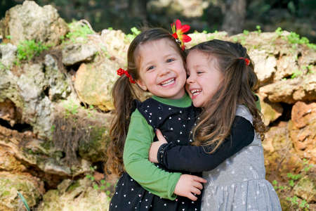 Cute twins girls are hugging each others at the nature background