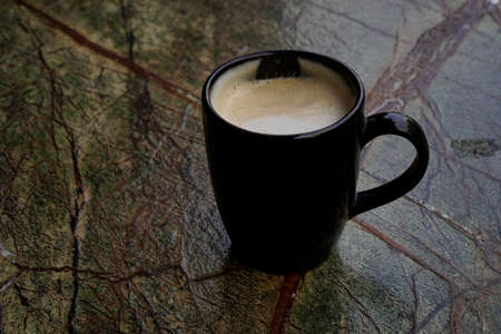 Black coffee cup with coffee on colorful background