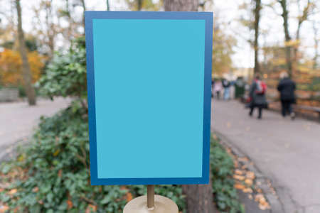 Empty blue sign board at park area. People walking around it.