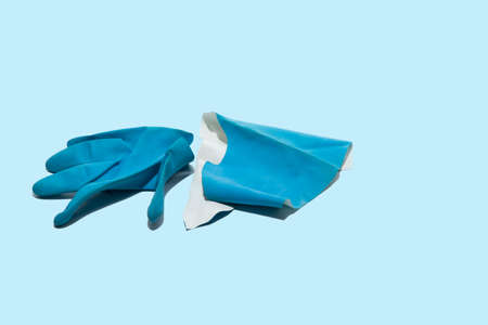 Worn, torn blue medical glove on a light blue background. Health professionals work under very difficult conditions. Stock Photo