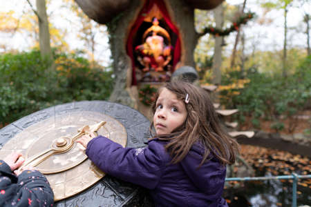The little girl looks a little scared in the fairytale playground. Stock Photo