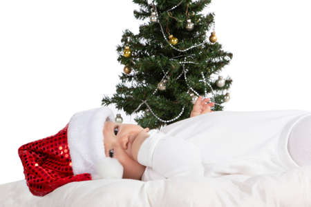 Cute baby girl is laying front of newyear tree with red christmas hat. White background. Stock Photo