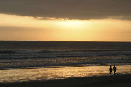 kuta: Sunset and runners at Kuta Beach Bali