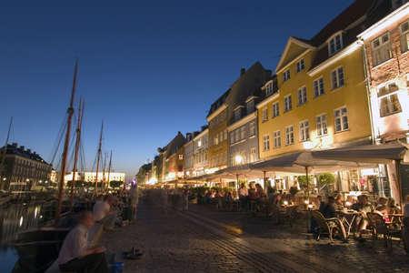 streetlife: Nyhavn harbour by Night. Many bars and restaurants. Copenhagen, Denmark Stock Photo