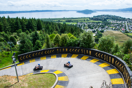 View of two cars at Skyline Luge Rotorua with lake and island in the background. Stockfoto