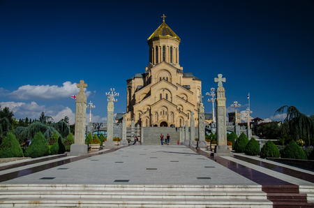 Front view of Holy Trinity Cathedral in Tbilisi with blue sky above.