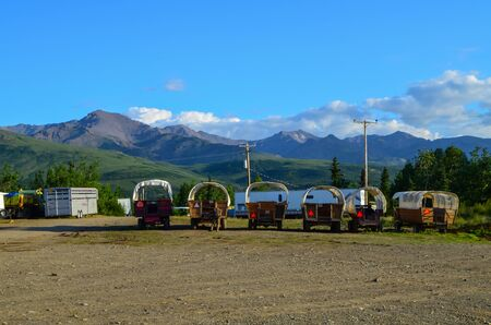 Wells Fargo horse wagons with mountains in the background and sunny blue sky above. Healy, Alaska, United States.