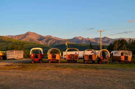Wells Fargo horse wagons with mountains in the background and sunny blue sky above during sunset golden hour alepnglow. Healy, Alaska, United States.
