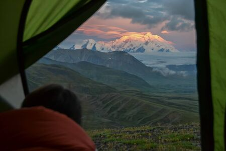 Person looking from a tent at sunrise view of Mount Denali (mt Mckinley) peak with red alpenglow at Stony Dome overlook. Denali National Park and Preserve, Alaska, United States