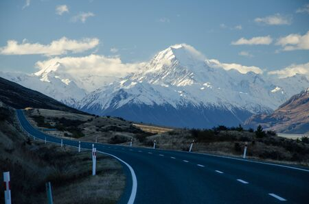 Snow covered Mount Cook with road in the foreground amd blue sky and white clouds, South Island, New Zealand. Banco de Imagens