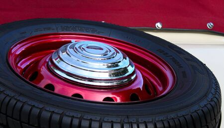 Old ancient car tyre, full of chrome, metallic cherry photo