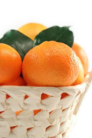 Dulce mandarina aislado en cesta blanca