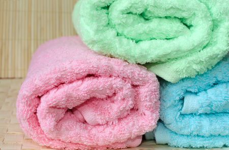 Three rolled towels, pink, blue and green  photo