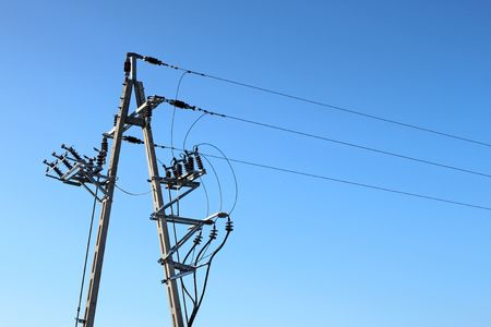 Power line tower against a clear, cloudless blue sky. photo