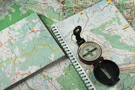 encuestando: Brújula negro, militar sobre los mapas detallados como fondo.  Foto de archivo