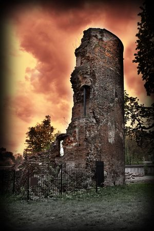 Mystic, ruined witch tower against red wild sky.